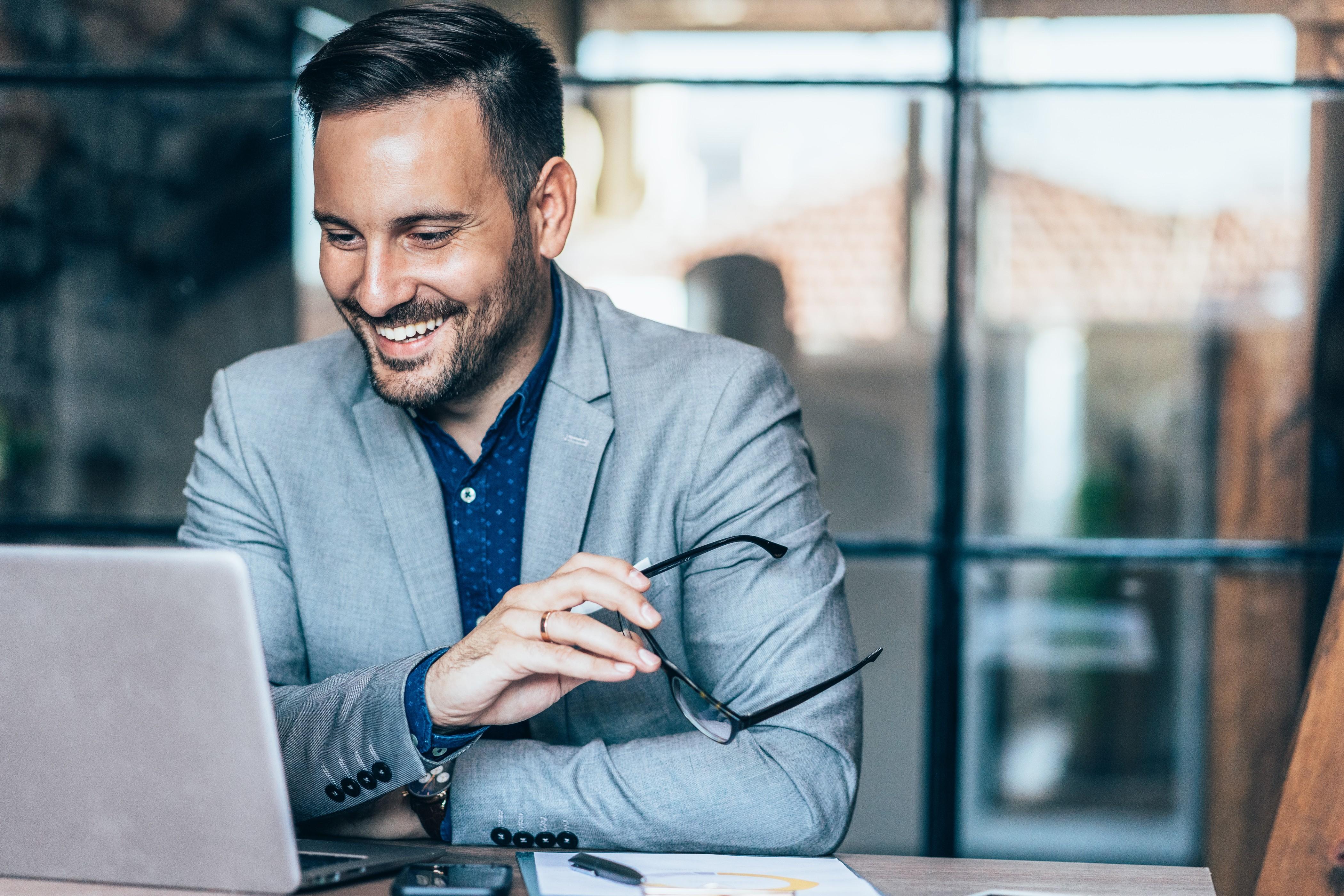 Man-in-suit-smiling-at-laptop-computer